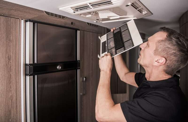 A man cleans vents in an RV by removing the cover.