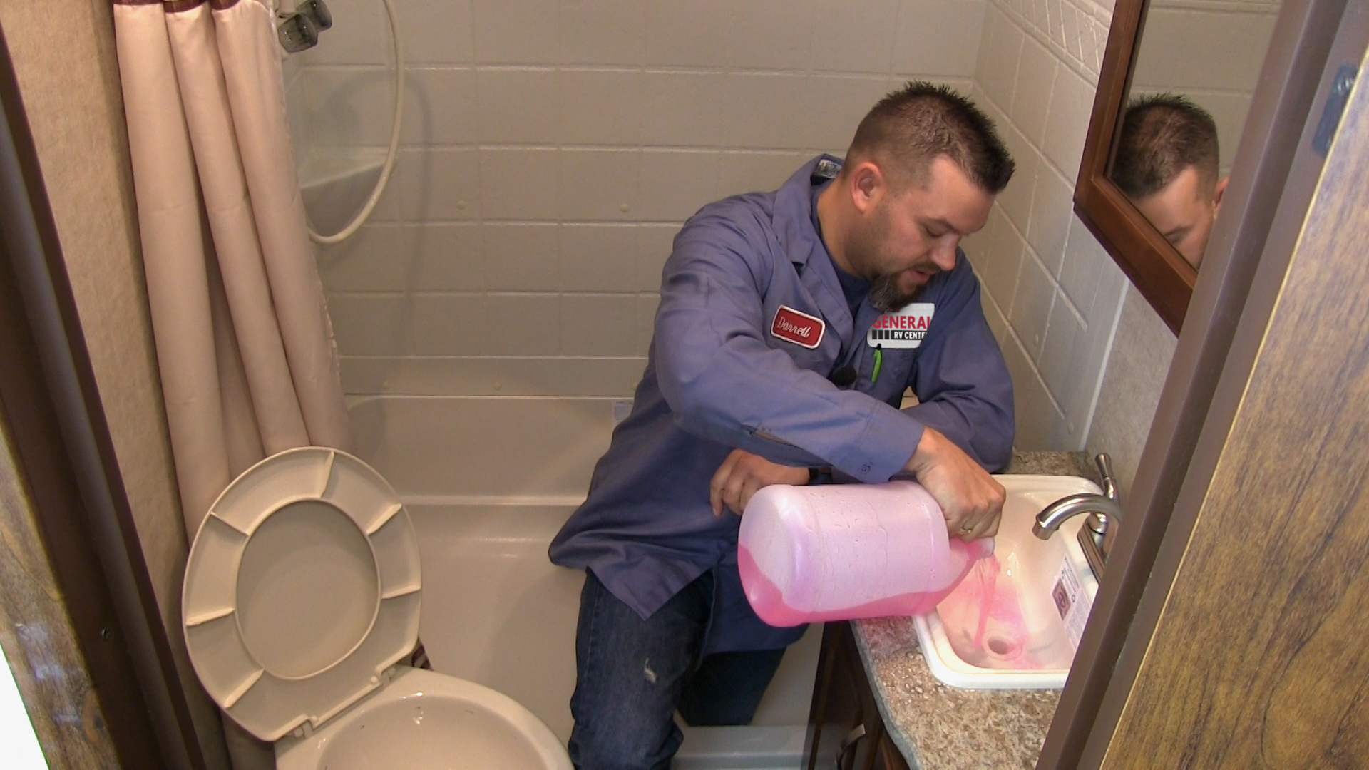 A man pours RV anti-freeze in sink drains to winterize the RV's plumbing.
