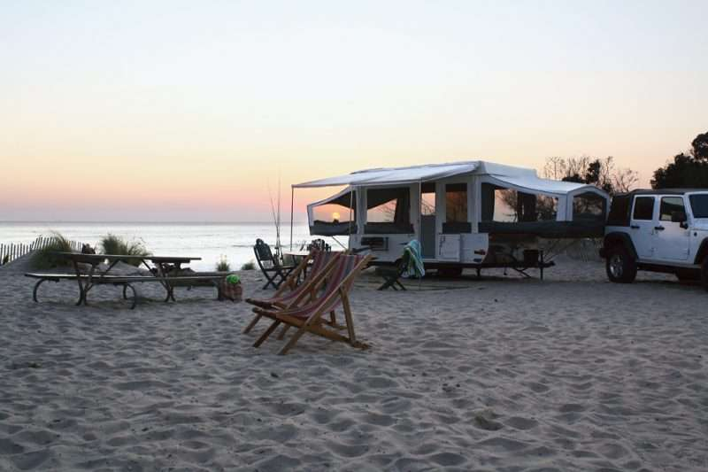 a popup trailer sits on the beach at sunset
