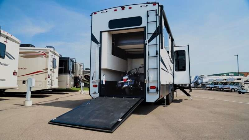 A motorcycle sits in the garage of a toy hauler RV