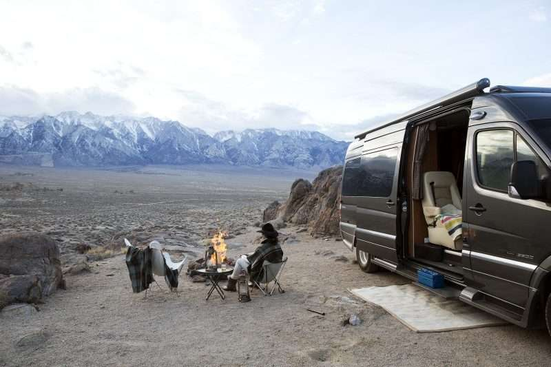 A Class B motorhome (B-Van) parked in the desert with mountains in the distance