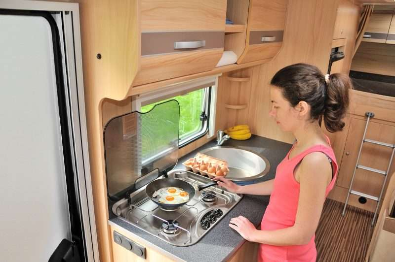 A woman cooks eggs in a pan over an RV cooktop. Making healthy meals affordably and avoiding eating fast food is a benefit of camping in an RV.