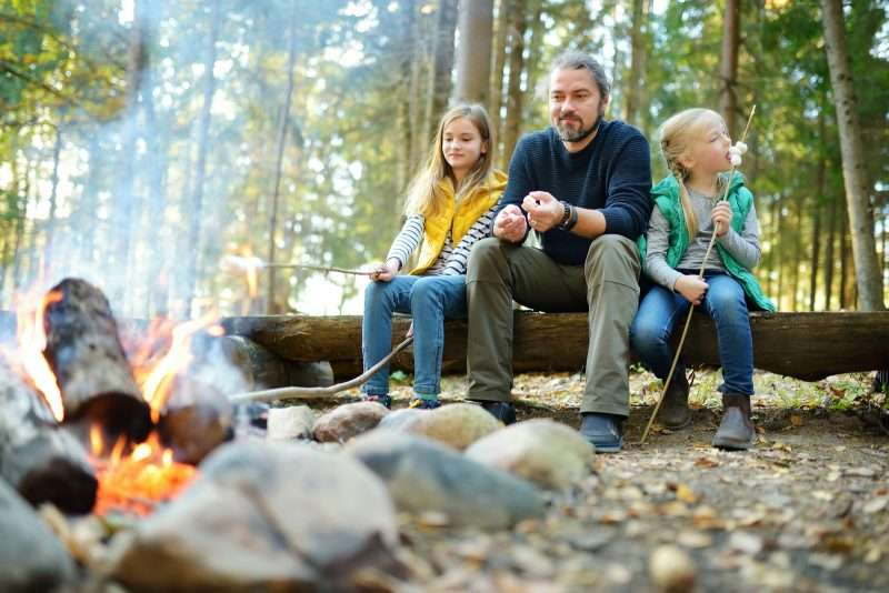 A father and his daughters roast marshmallows over a campfire Spending time together, making memories, and creating your own traditions - these are just a few of the benefits of camping!