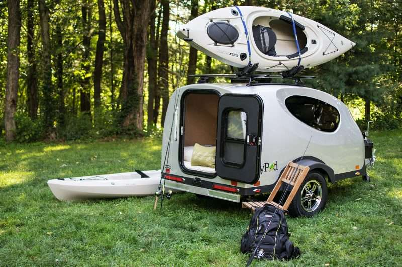 a small camper called the MyPod sits in the woods with fishing equipment and kayaks nearby