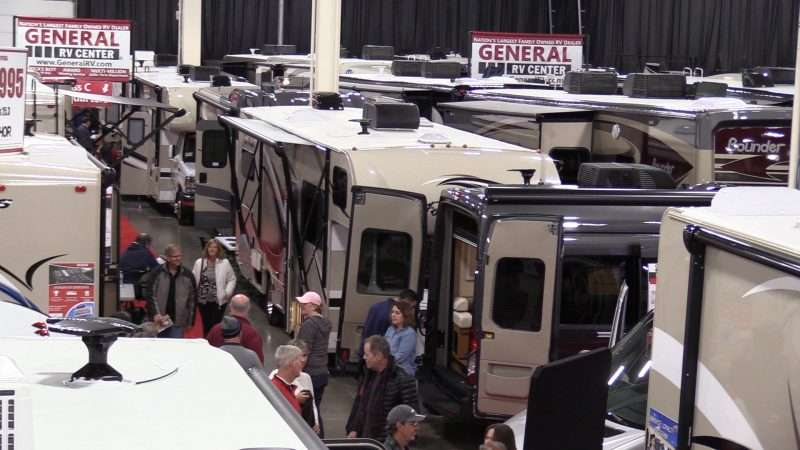 Many RVs are setup with doors open and on display inside a convention center during an RV show. Attendees are walking in the aisle and looking at the different RVs.