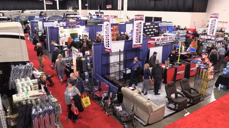 Several men and women walk the aisles of a large convention center where booths filled with RV accessories are on display. The booth in the foreground shows RV chairs and other accessories. There are RVs visible on the far left and in the background.