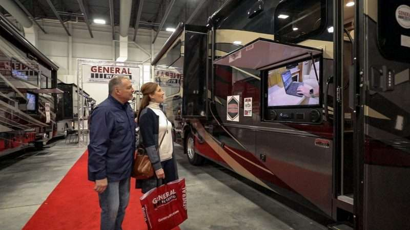 A man and woman are watching a video that's playing on a TV mounted to the exterior of a large RV. The RV is set up inside a convention center for an RV show.
