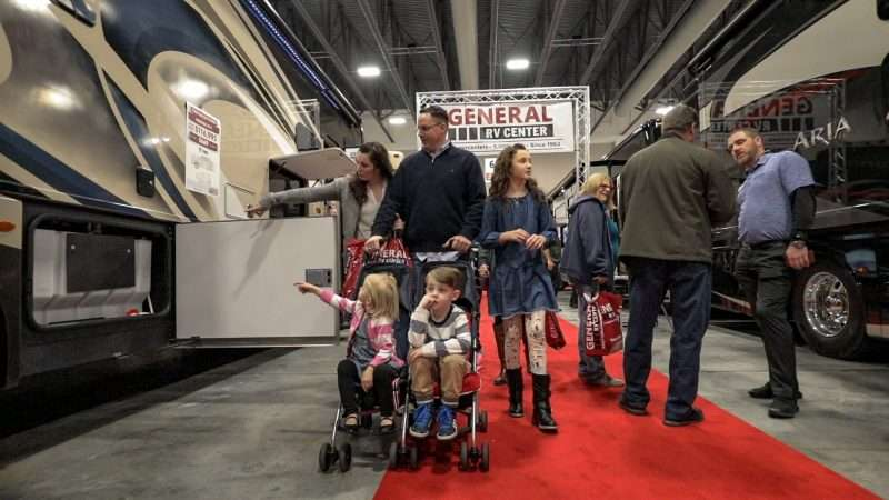 A family with a mother, father, older daughter, and two younger children attend an RV show. The youngest boy and girl and sitting in a stroller and being pushed by their father. The mother and older daughter are looking at display RVs on either side of the aisle. They are walking past another couple speaking with a manufacturer representative.