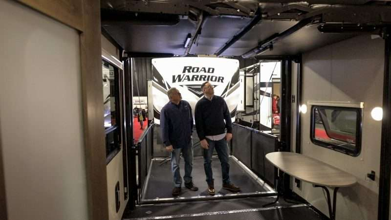 Two men stand inside an RV on display at an RV show. They are looking at two retractable bunks that can be lowered from the ceiling and double as beds. The RV they are looking at also has a fold-down rear door that doubles as a deck patio, complete with railing.