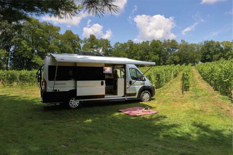 A Thor Sequence class b motorhome sits at the edge of a vineyard with the awning extended. A picnic blanket, with bottles of wine in a basket and one wine glass, is spread out on the grass under the awning.