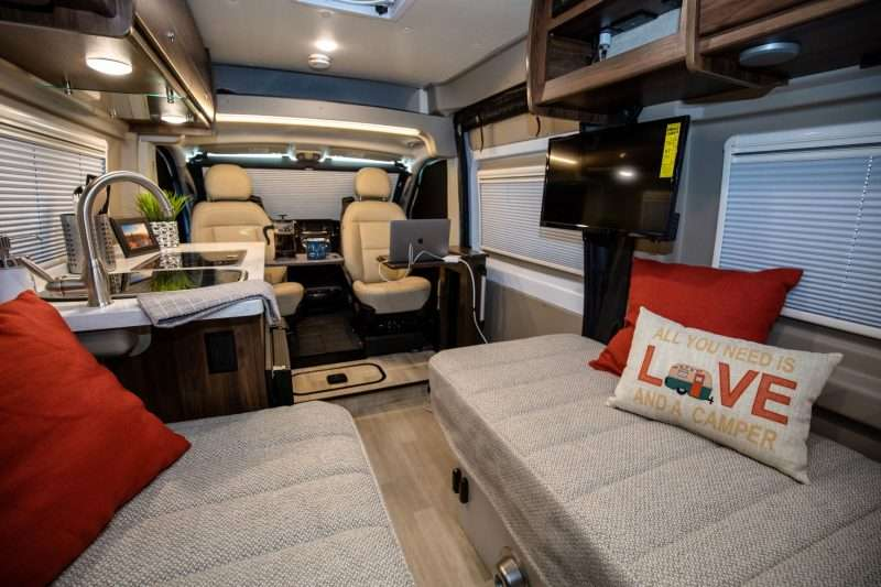 A photo of the interior of a Winnebago Travato camper van. The foreground has two bench seats with accent pillows opposite each other. Mid-cabin is a galley kitchen. At the front