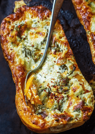 A butternut squash is cut in half and filled with a four cheese and spinach mix in this easy holiday recipe. The edges of the cheese filling are browned and a spoon is piercing the squash as if getting ready to serve.