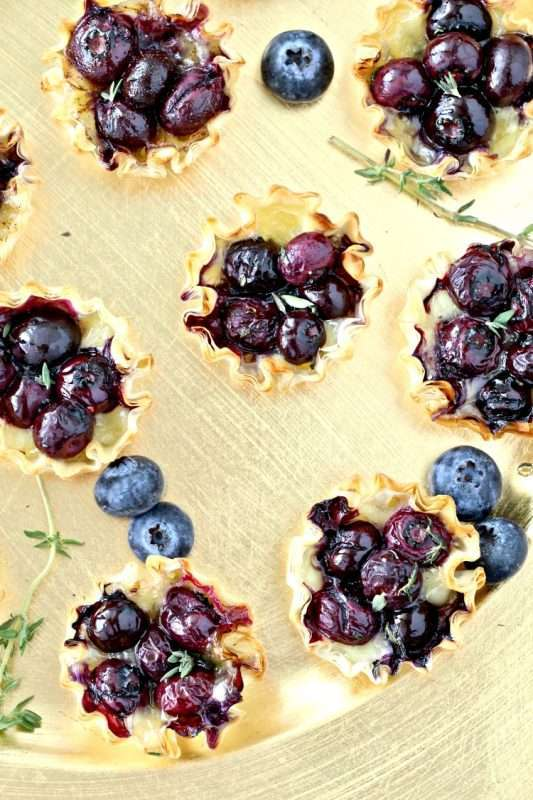 Blueberry Brie Bites are arranged on a gold plate and garnished with fresh blueberries and sprigs of chopped thyme.