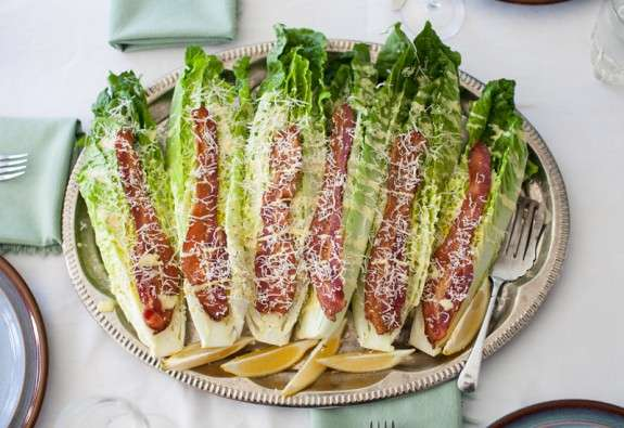 Spears of romaine lettuce are topped with strips of bacon, and Parmesan cheese to make caesar wedge salad with bacon. The salad is arranged on a metallic plate and garnished with lemon wedges.