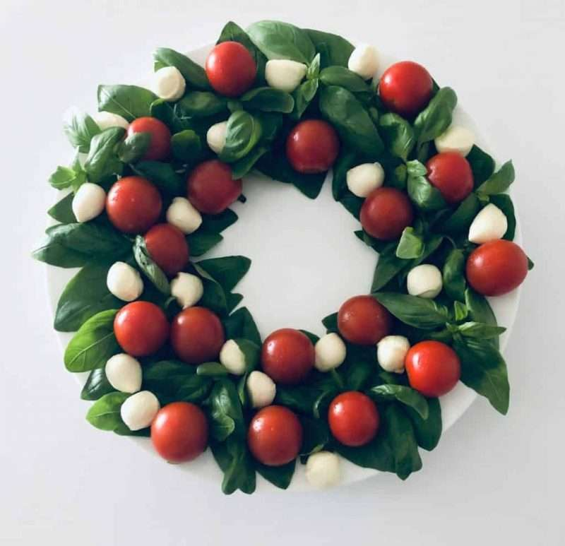 Mozzarella balls and cherry tomatoes are arranged on a bed of greens shaped as a festive wreath for an easy holiday salad recipe.