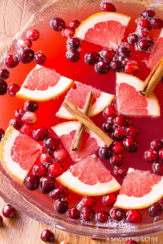 A glass punch bowl is filled with Champagne Holiday Punch. Wedges of cut grapefruit, fresh cranberries, and three cinnamon sticks float on the surface of the punch.