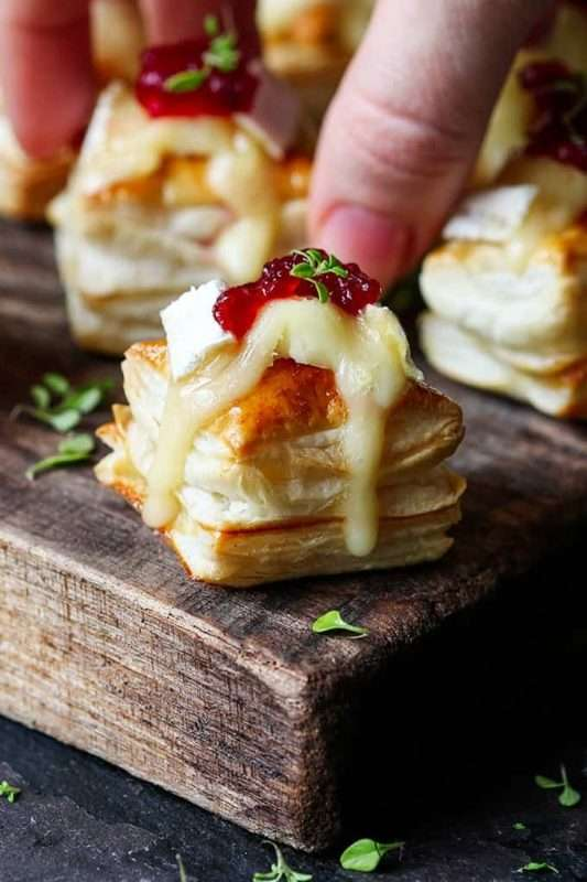 A hand reaches down to grab a Cranberry Brie Bite arranged on a wooden serving tray.