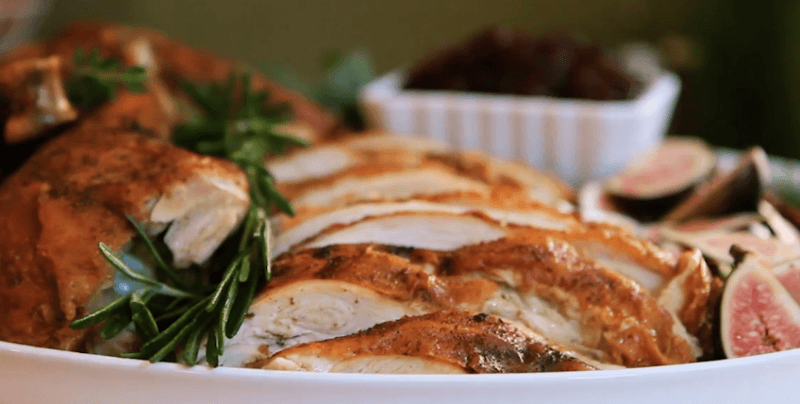 A white plate is filled with carved slices of a deep fried turkey garnished with sprigs of rosemary and sliced figs.