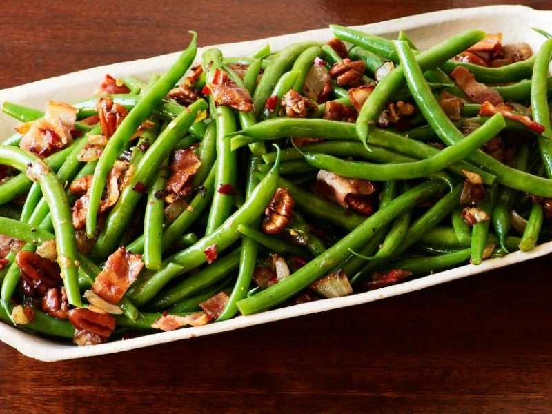 A white serving platter is filled with cooked green beans and bacon. Chopped pecans are added to top off this easy holiday side dish.