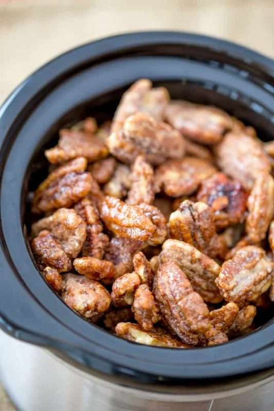 A crock pot is filled with candied cinnamon pecans.