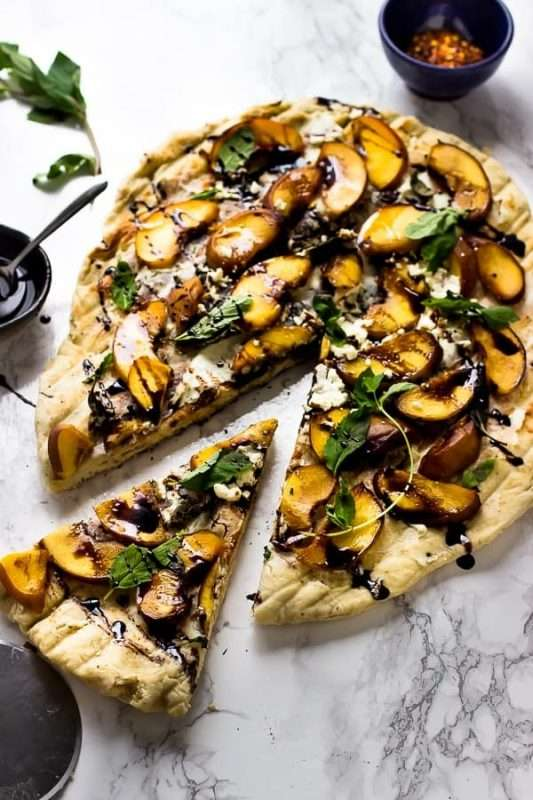 A round pizza topped with grilled peaches, basil, and vegan goat cheese sits on a white and gray marble counter top. A slice of the pizza has been cut and is arranged near the rest of the pie.