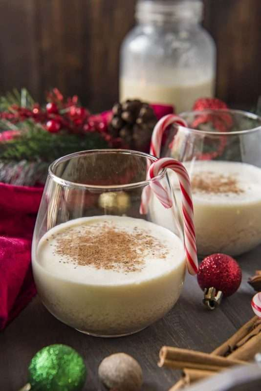 Two glasses of eggnog sit on a table surrounded by holiday decor, including miniature ornaments and  pine cones.