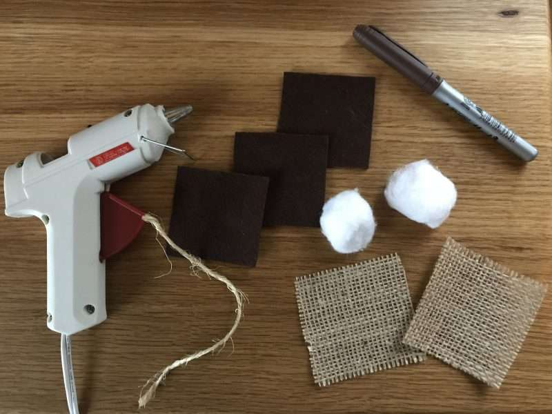 Craft supplies to make a S'mores ornament are arranged on a wooden table top. There is a craft glue gun, three brown squares of felt, two white cotton balls, two squares of burlap, a small piece of twine, and a brown marker.