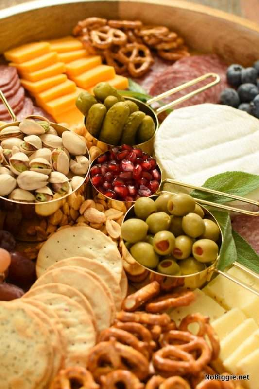 A DIY Charcuterie Board is an easy recipe to make for holiday gatherings. A wooden charcuterie board is filled with various cheeses, meat slices, pretzels, and crackers. In the center of the board are metallic measuring spoons containing pistachios, pickles, green olives, and dried cranberries.