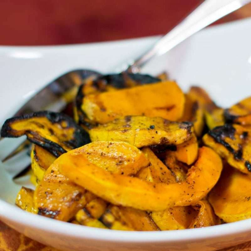 Grilled pieces of butternut squash fill a white bowl.