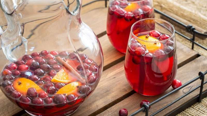 A near-empty glass pitcher and two full glasses of Spiced Cranberry Sangria sit on a wood and metal serving tray.