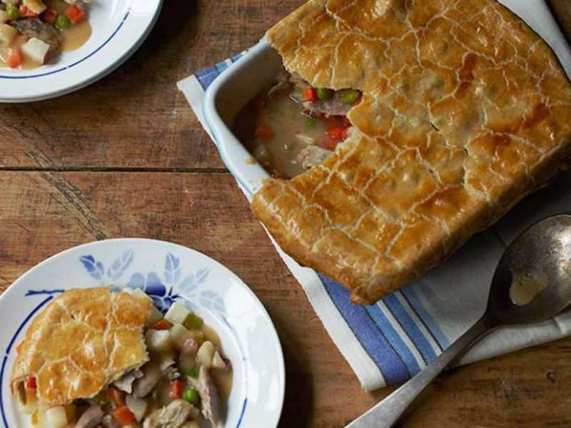 A turkey pot pie is served on a wooden table. There is a large casserole dish with the turkey pot pie on the right side of the image and two plates filled with portions of the turkey pot pie are on the left.