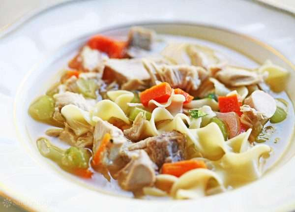 A white bowl is filled with Turkey and noodle soup. There are large chunks of carrots, celery and turkey meat alongside the egg noodles.