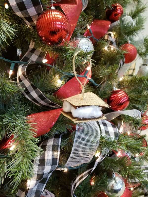 A handmade S'more ornament hangs on the branch of a large green pine tree. The ornament is made of burlap, brown felt, and white cotton balls with a twine hanger glued to the top. The tree is decorated with white and black plaid ribbon, red ribbon, and sparkling silver ribbon. There are red and silver bulb ornaments hanging around the S'more ornament.
