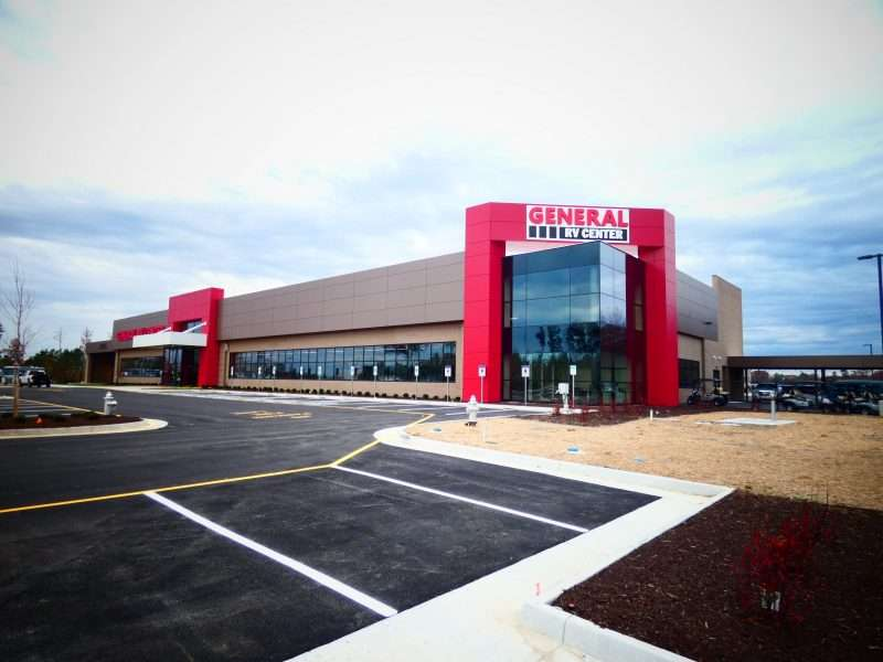 General RV's new Ashland dealership as viewed from the parking lot. The facility consists of a large rectangular building with tan bricks, large glass windows, and red accents.