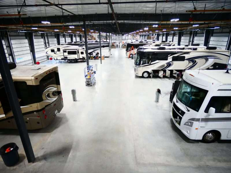 An interior photo of General RV Ashland's service area. Several motorhomes and one travel trailer are lined up in service bays.
