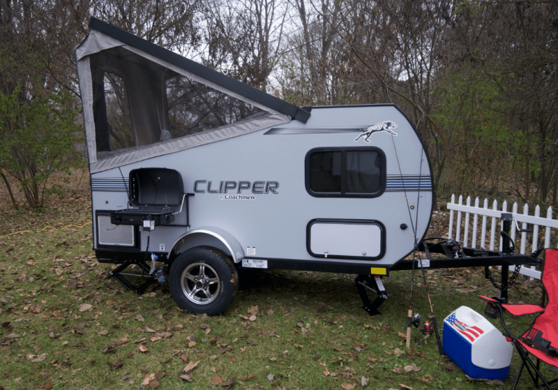 A Clipper camper trailer with a fold-down roof is parked at a campground. There is a camp chair, cooler, and two fishing poles sitting next to the RV.