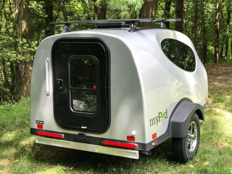 A silver MyPod teardrop trailer is parked at the edge of a wooded area.