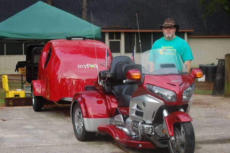 A red MyPod trailer is towed behind a matching red Honda trike motorcycle. A man in a green t-shirt and brown western hat stands next to the motorcycle.