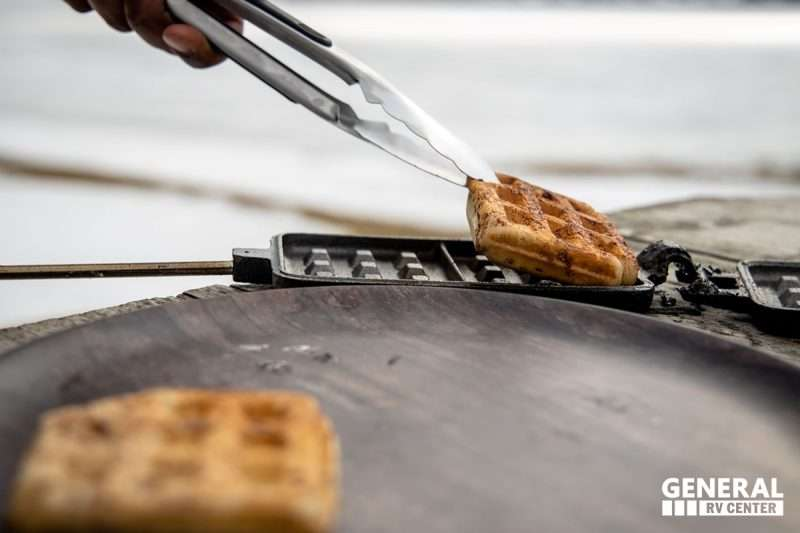 A man uses metal tongs to remove cinnamon rolls from a hot iron.
