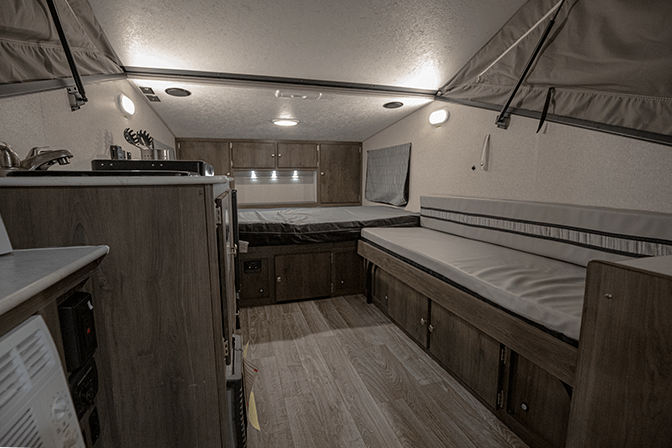 A view from the rear entrance of the Coachmen Clipper 12.0TD XL pop up camper RV shows the kitchenette on the left, the gaucho on the right and the main bed at the front of the trailer.