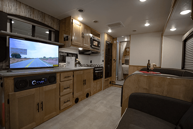 A photo of Coachmen RV's Leprechaun 319M RV interior shows off it's modern decor. Light, cherry colored cabinets with dark hardware, dark fabrics, and black appliances.