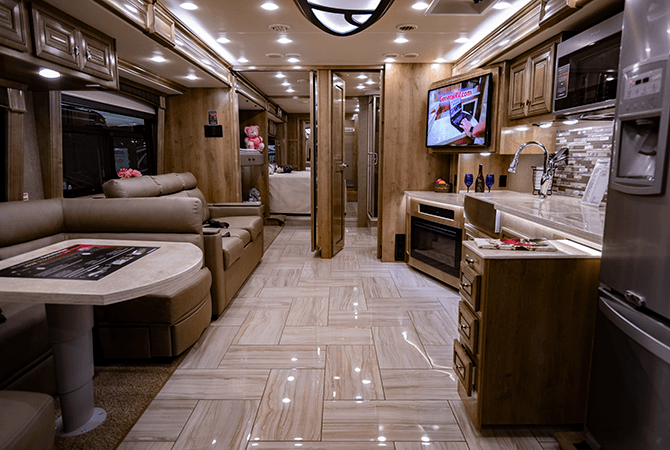 A view from front to back inside the Discovery LXE 40G motorhome by Fleetwood RV. This RV floor plan features a wide open living and dining area. Midway back into the RV, a set of folding doors reveals a bunkroom on the passenger side and a bathroom on the driver's side of the coach.