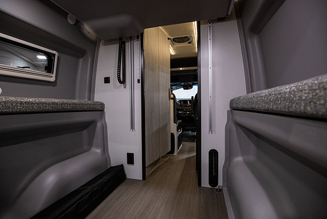 A photo from the rear of the Winnebago Revel 44E Class B RV Camper Van shows the power lift bed raised to reveal the large garage area.