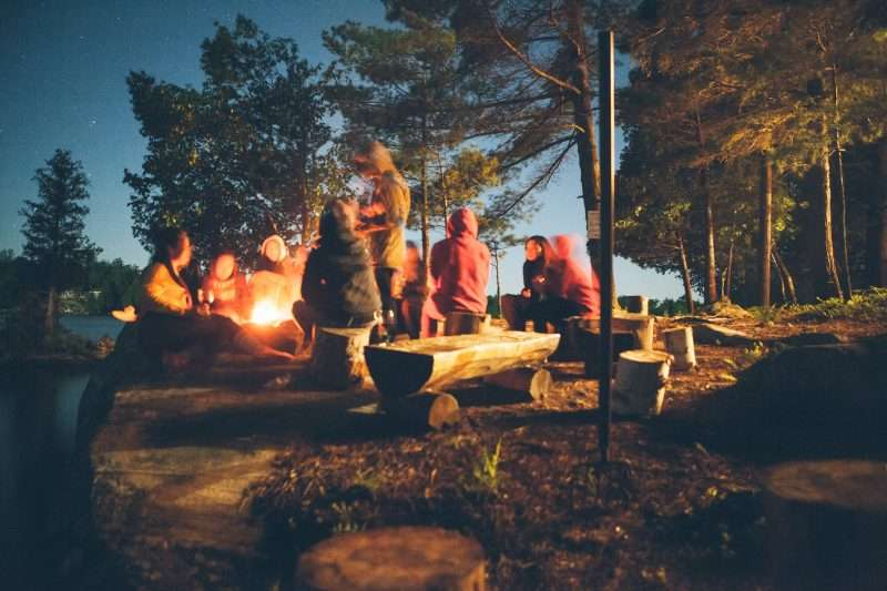 People gather around a campfire at night.