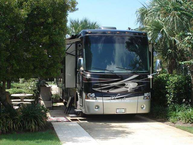 A Class A motorhome RV on a campsite at the Destin RV Beach Resort campground in Florida.
