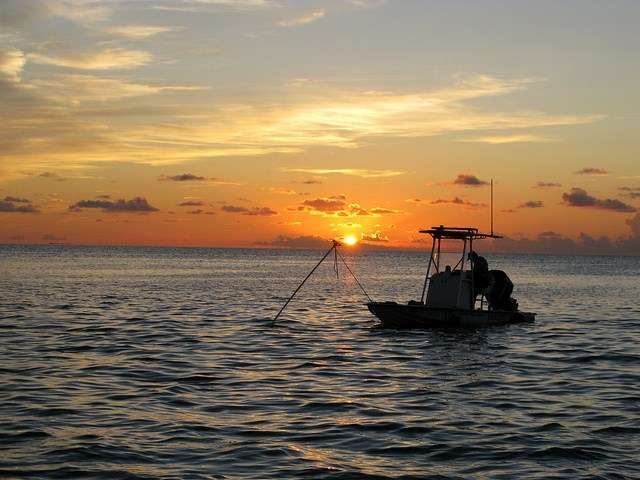 A fisherman in a small center console boat at sunrise.