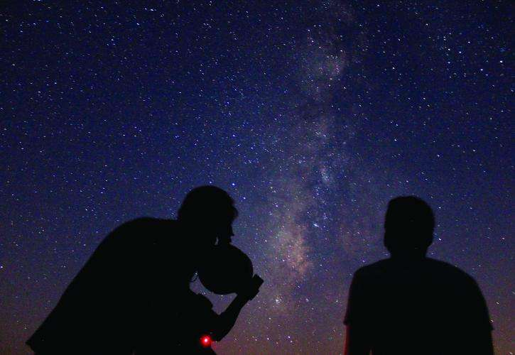 Two people observe the night sky filled with stars at Kissimmee Prairie.