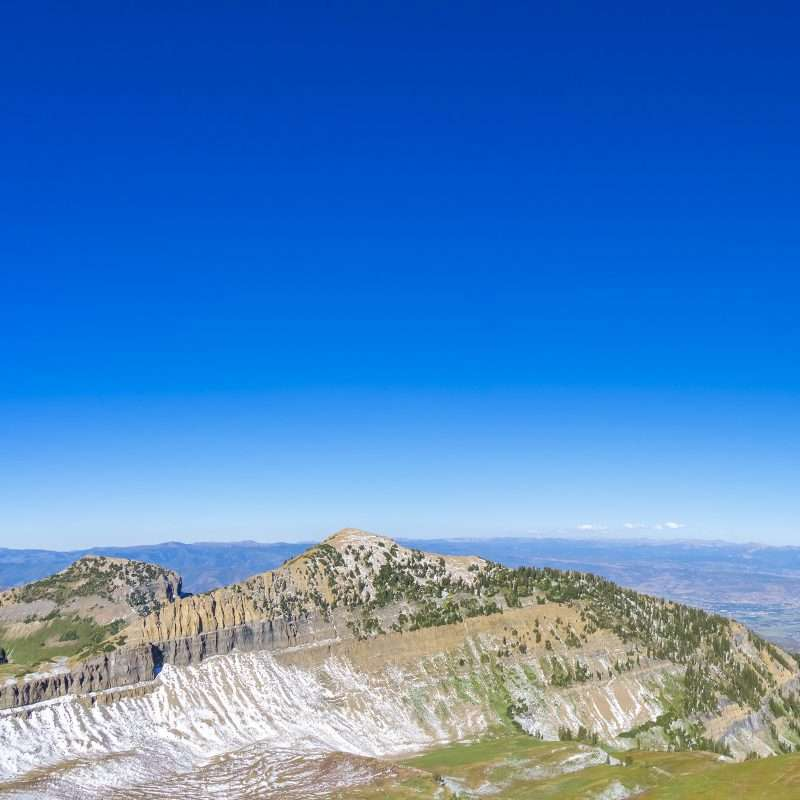 The summit of Mount Timpanogos, Utah, as see during daylight. The sky is a brilliant blue and almost completely cloudless. The Mountain is dotted with green trees and ridges of white snow making for a magnificent scene.