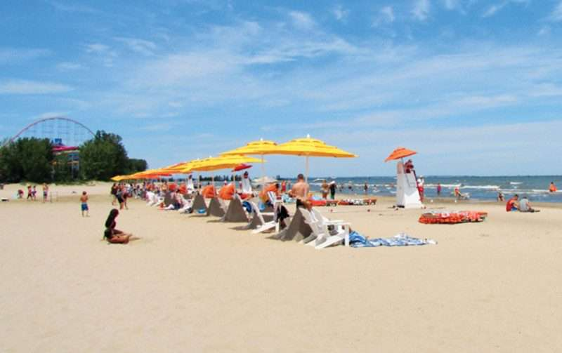 A line of beach goers in white beach chairs at Cedar Point Beach during the summer. The sky is bright blue with wispy white clouds.
