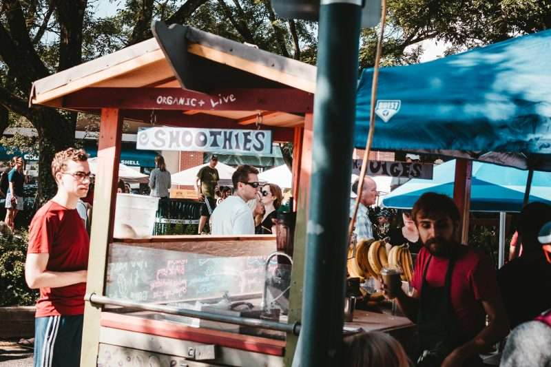 Several people wander through a group of food stands. In the foreground of the photo, a man waits at a smoothie stand while a vendor prepares his drink.